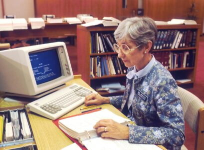 Elderly lady on retro computer in library studying