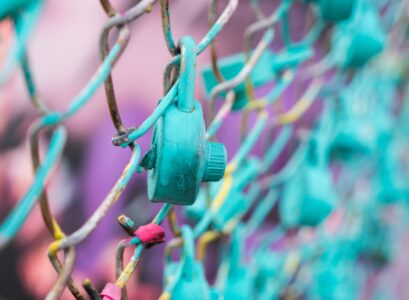 teal padlock on link fence