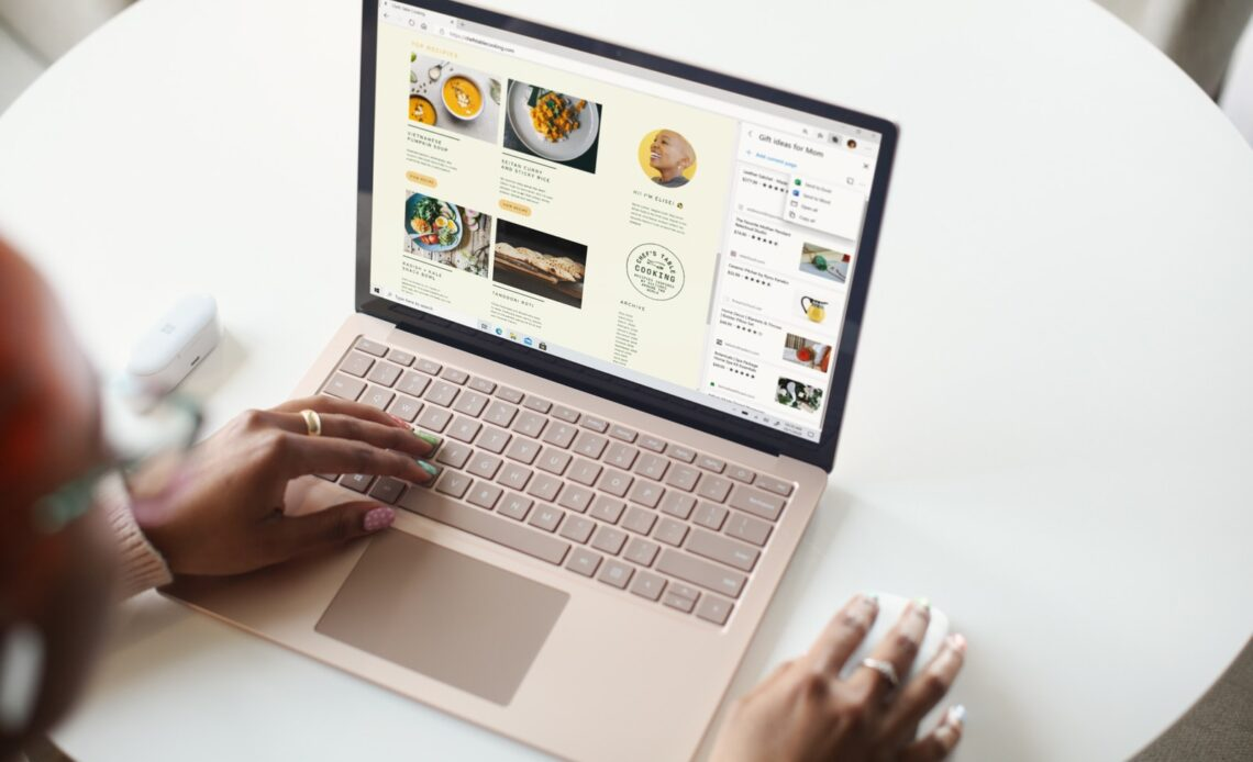 person using Surface laptop on white table