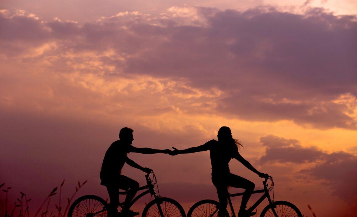 Woman on Bike Reaching Out